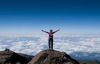 Trekker above cloud at the summit of Mount Kilimanjaro