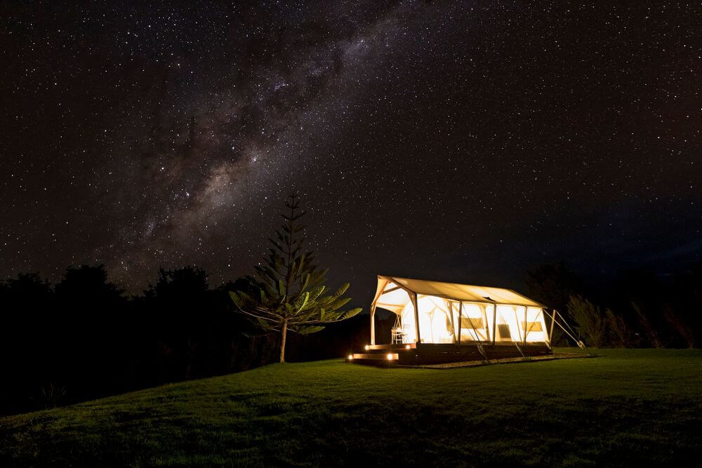 luxury campsite lit up underneath the starry night sky