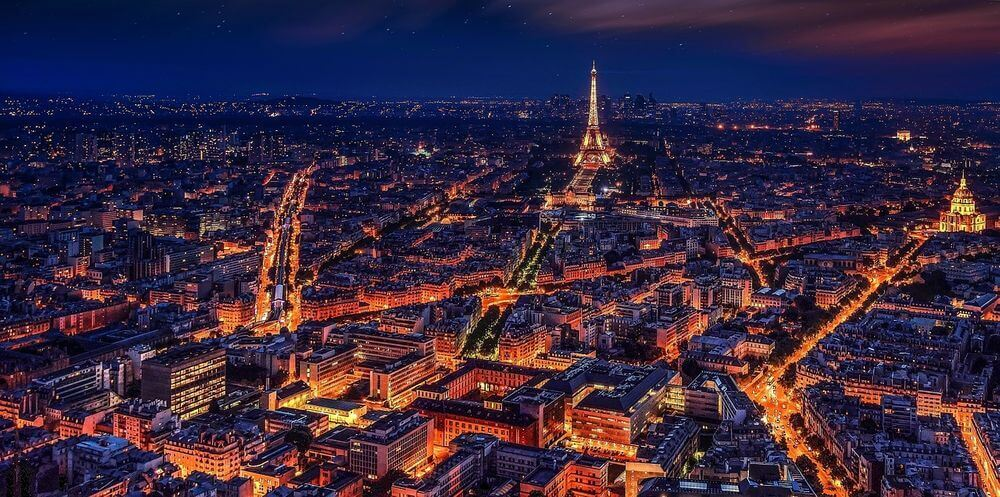 aerial view of Paris and the Eiffel Tower lit up at night