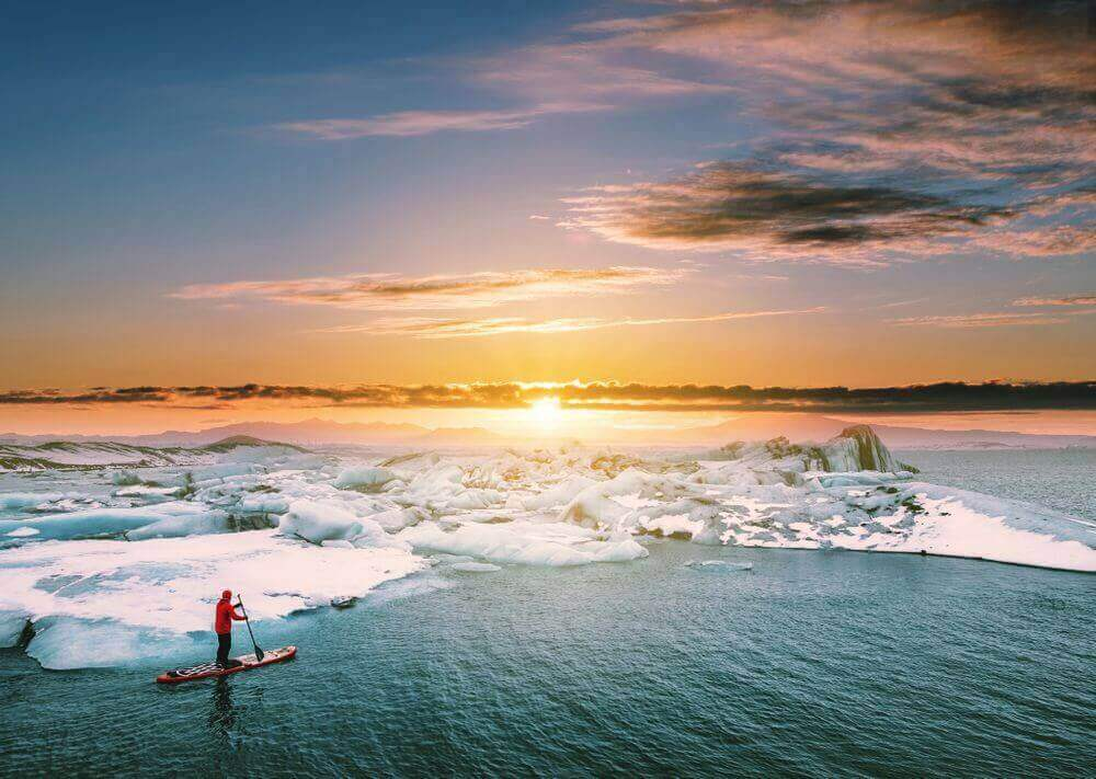 traveller stand up paddleboarding in antarctica at sunrise