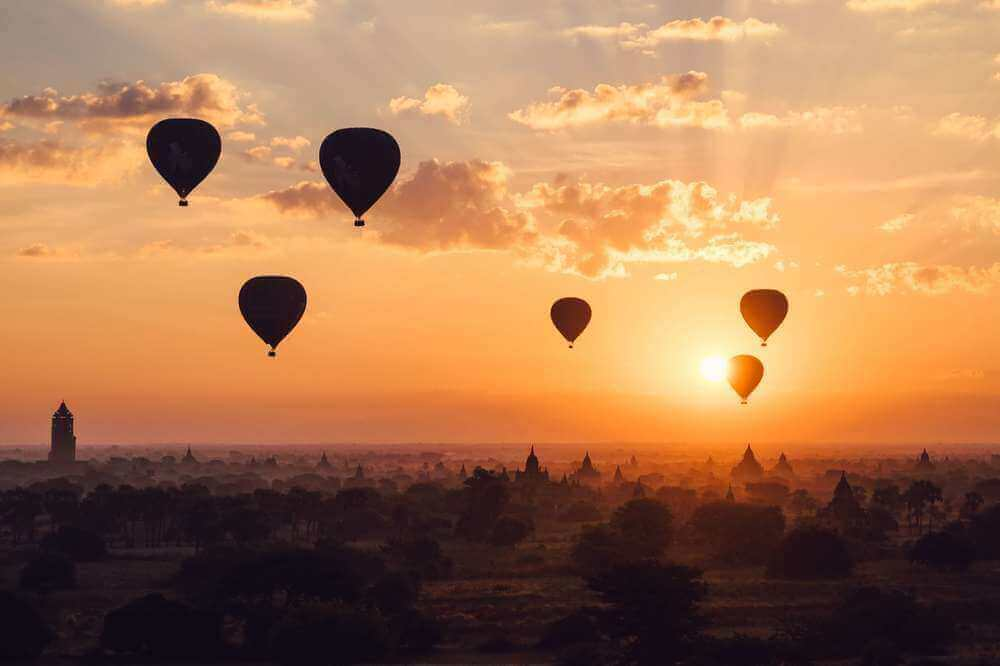 hot air balloons floating over ancient temples at sunrise in bagan myanmar