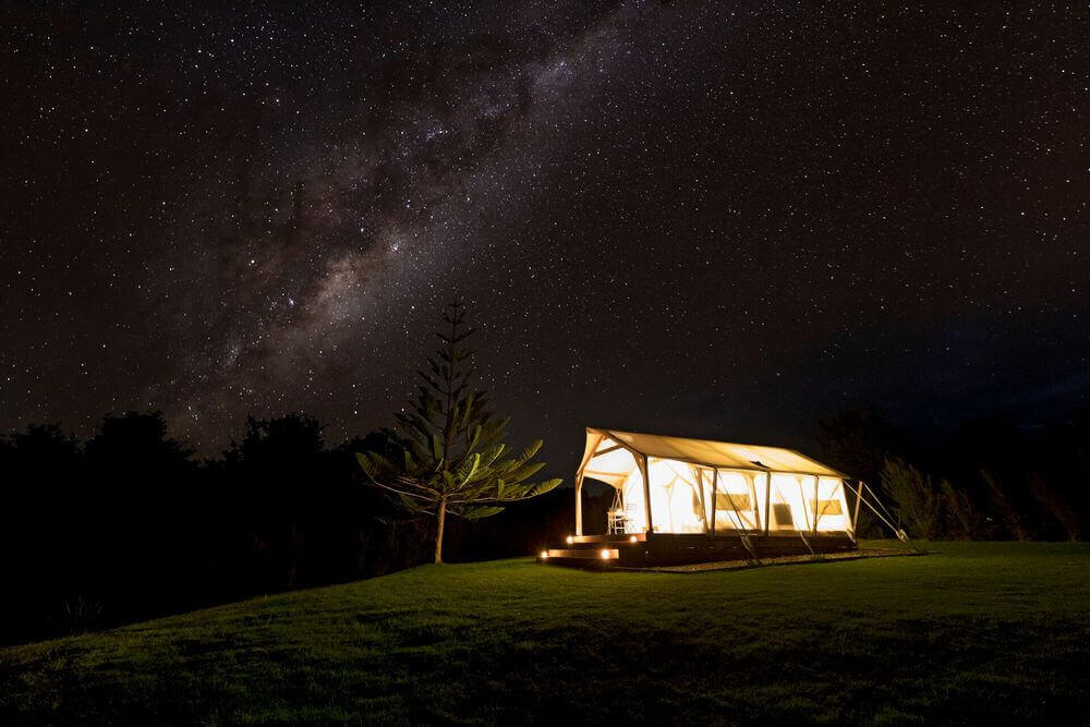 magic cottage luxury camping site lit up beneath the starry sky takou river new zealand