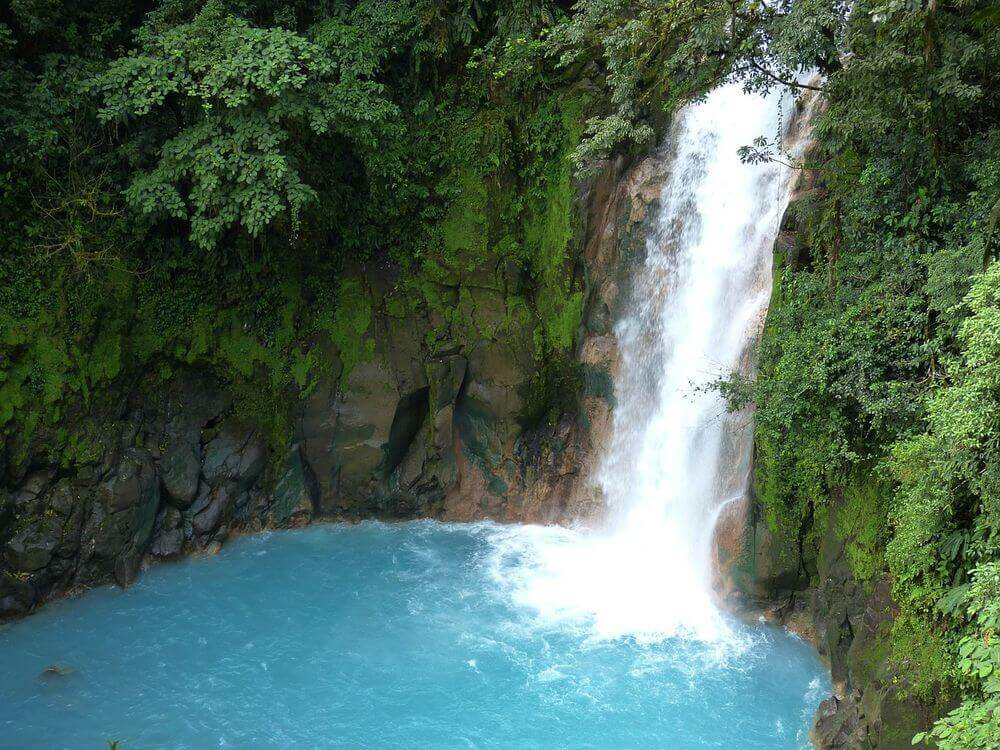 bright blue water surrounded by green jungle of a waterfall in costa rica