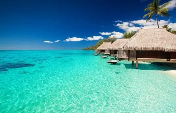 overwater villas in the crystal blue waters of the maldives