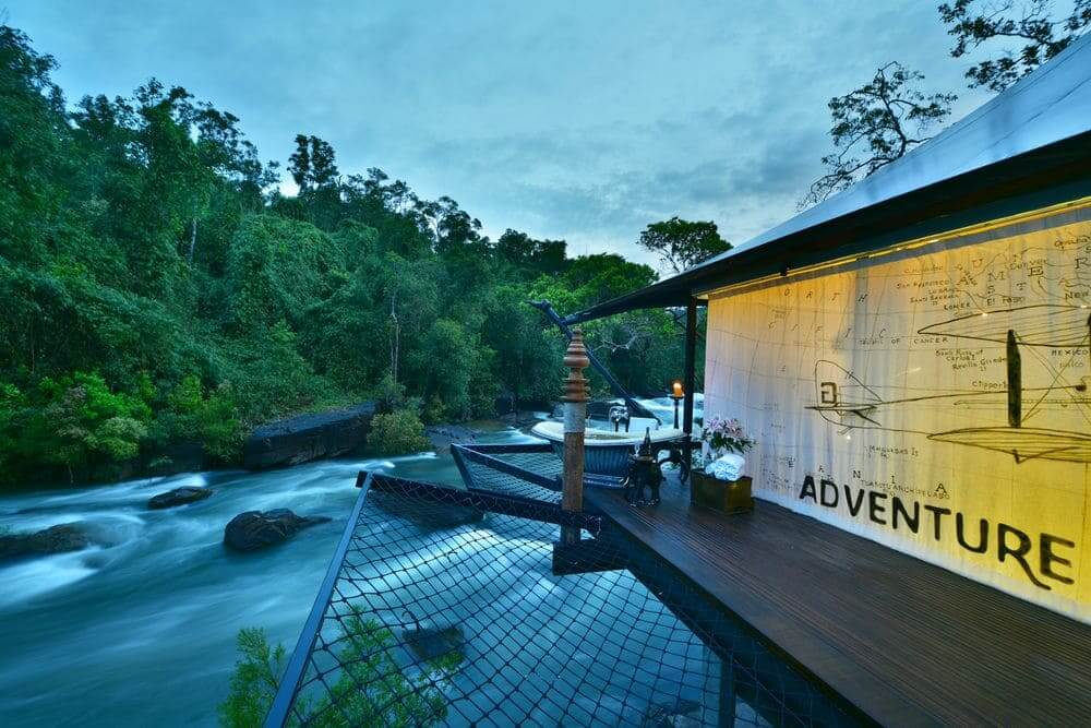 outdoor bathtub perched over the river with adventure mural