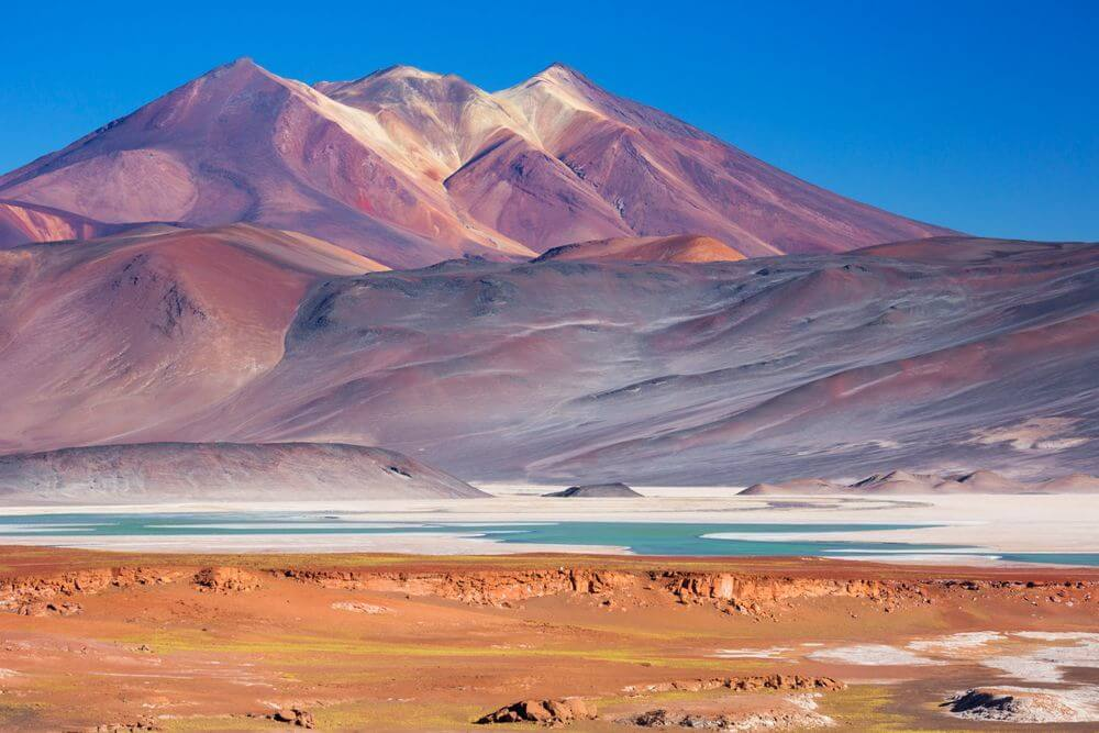 colourful red mountains and dazzling blue lakes in the salt flats of Atacama Desert