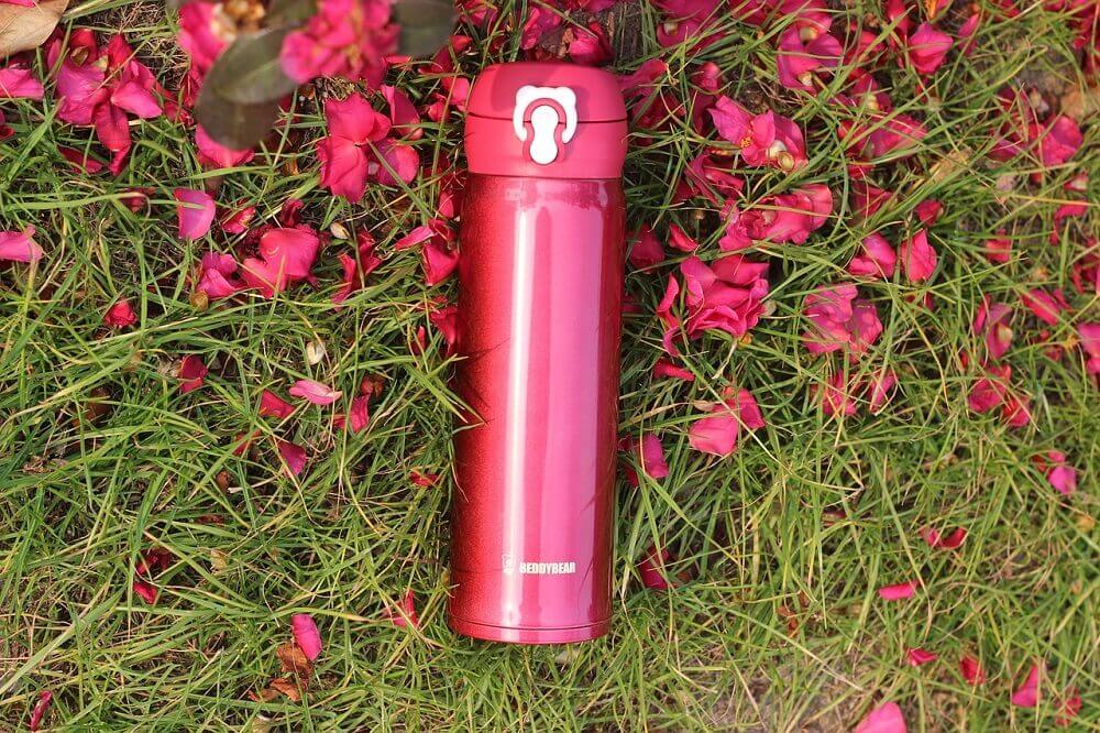 Pink reusable water bottle in grass