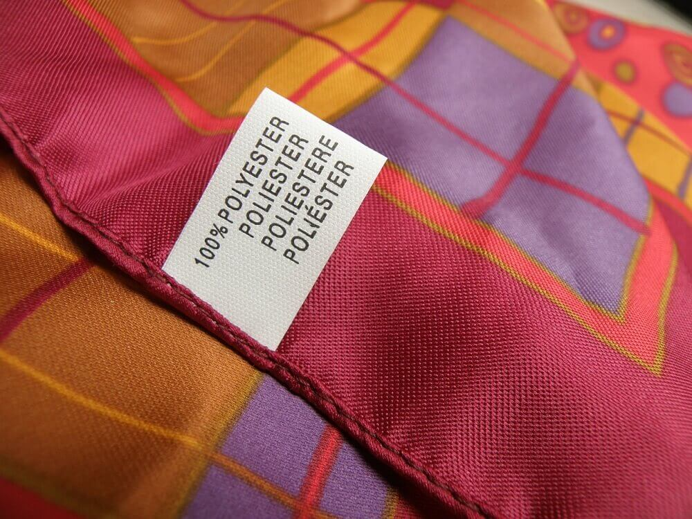 Scarf with label saying polyester - synthetic plastic material