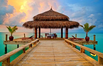 Tropical hut on the water at sunset on a Maldives honeymoon in Asia