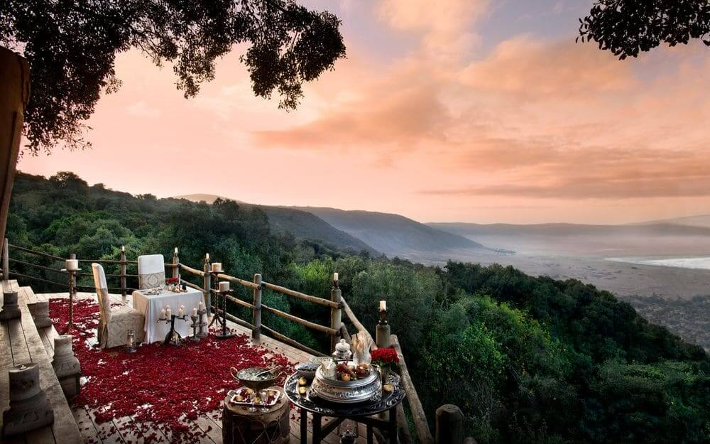 romantic sunset dinner with rose petals overlooking the might ngorongoro crater at ngorongoro crater lodge, tanzania