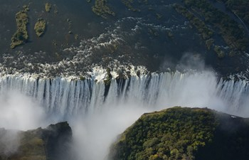 Drone shot of water gushing down in Victoria Falls