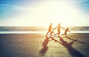 A family on holiday running across the beach