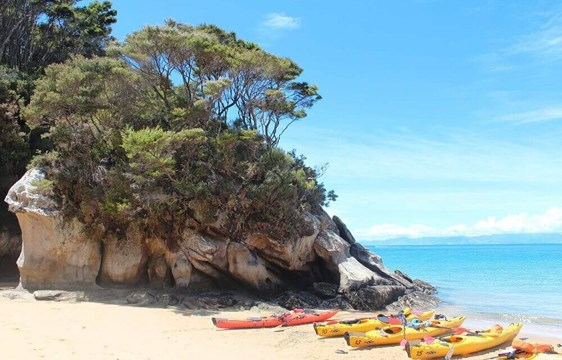 Kayaks on the beach in January in New Zealand's summer