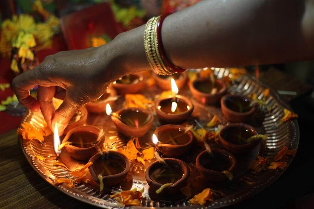 candles being lit for diwali festival of lights india