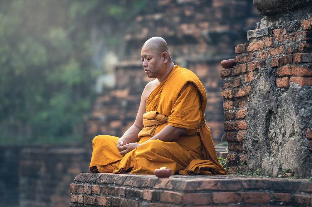 Buddhist monk meditating on a temple