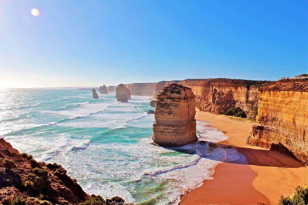 sunshine lighting up the orange rock of the twelve apostles in Vic