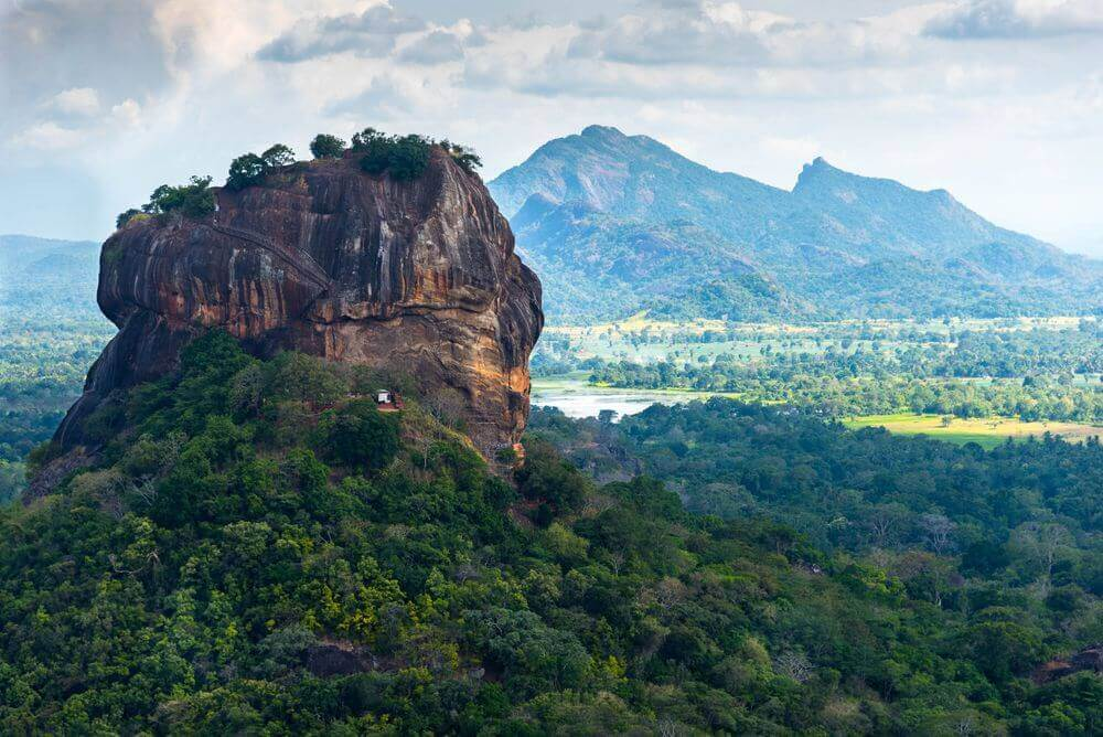 sigiriya lion rock rising through the lush forest in sri lanka