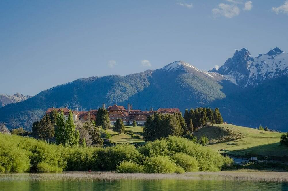 Llao Llao resort on the green lake shore with mountain backdrop bariloche argentina