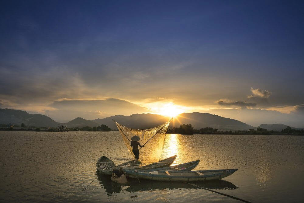 A fisherman casts his net at sunset in southeast Asia