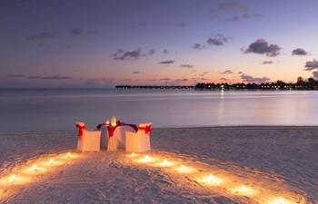 A Maldives honeymoon with a candle lit dinner on a beach