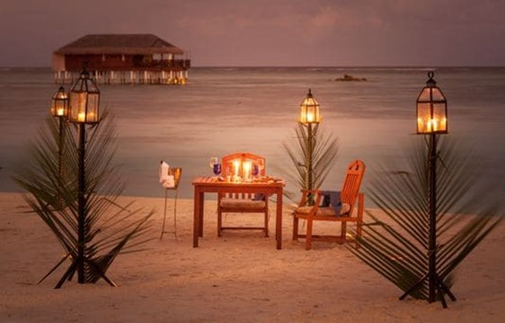 romantic candelit dinner on a beach in the maldives