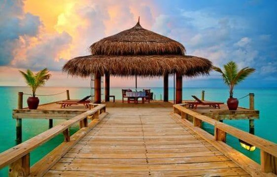 sunset over a tropical overwater hut in the maldives