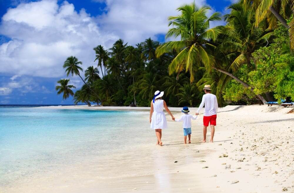 family walking along the palm fringed beach in the maldives