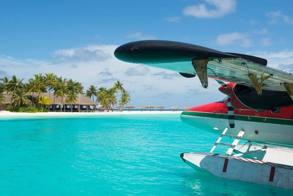 seaplane landing on the bright blue waters of the maldives