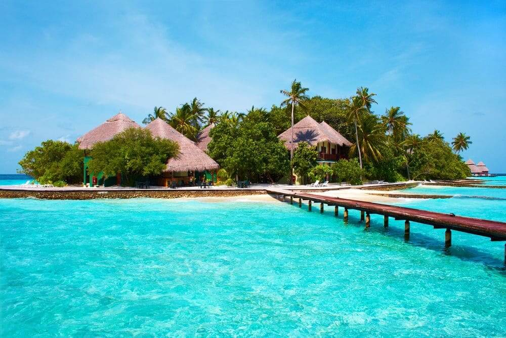 villas on an island surrounded by dazzling water in the maldives