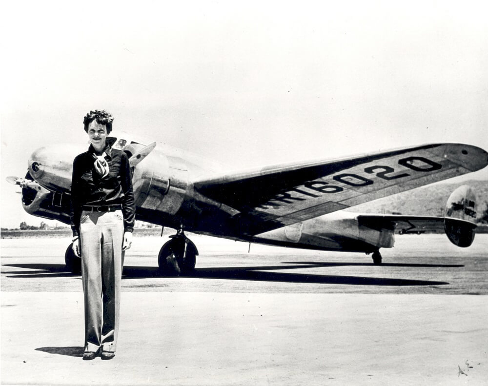 Amelia Earhart female aviator next to plane