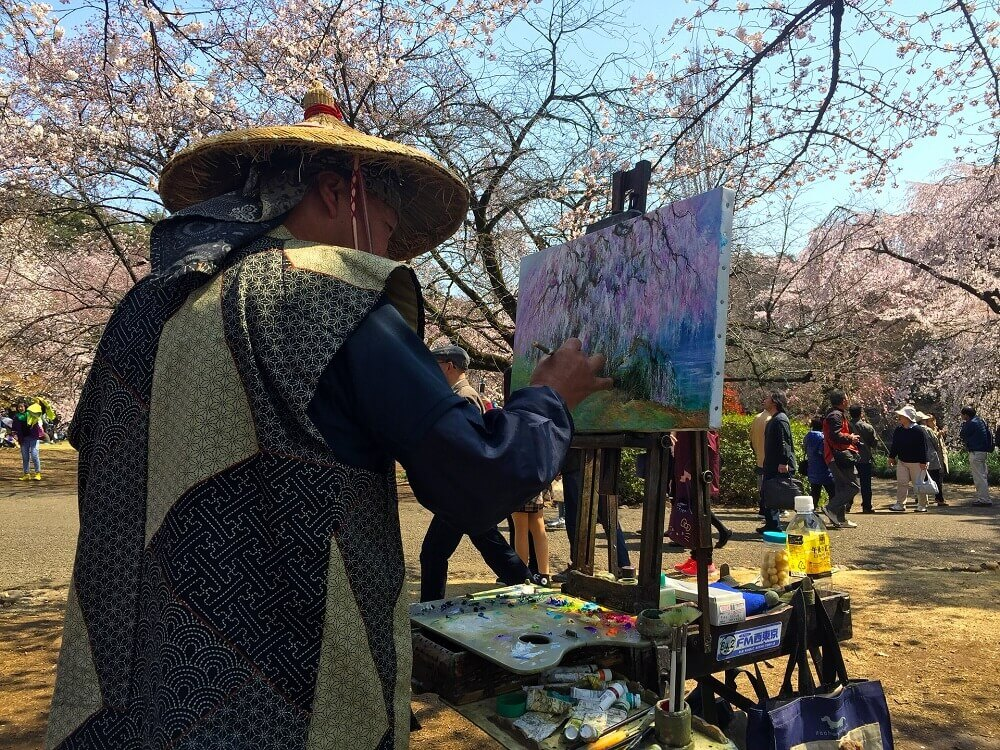 Japanese man painting sakura during cherry blossom viewing season in Japan