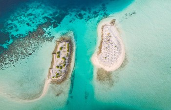 aerial view of white sandy islets surrounded by turquoise water in south ari atoll, maldives