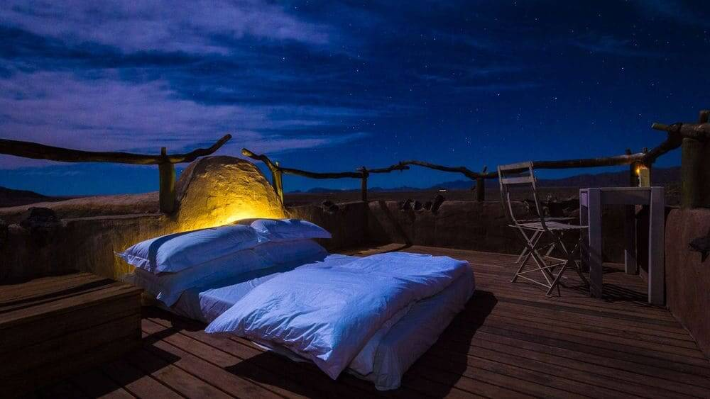 star bed under the night sky at Little Kulala, Sossusvlei, Namibia
