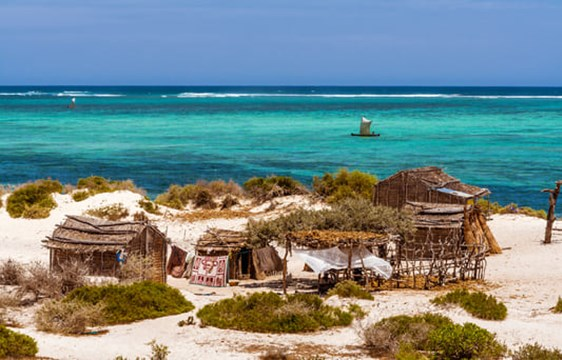 fishing village on a white sandy beach near crystal blue waters in Madagascar