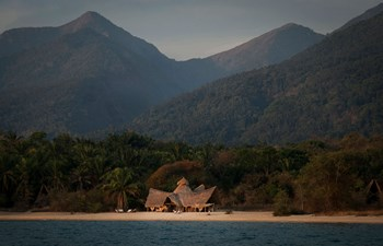 panoramic view of Greystoke Mahale Camp on the white sandy beach surrounded by forested mountains in Mahale Mountains, Tanzania